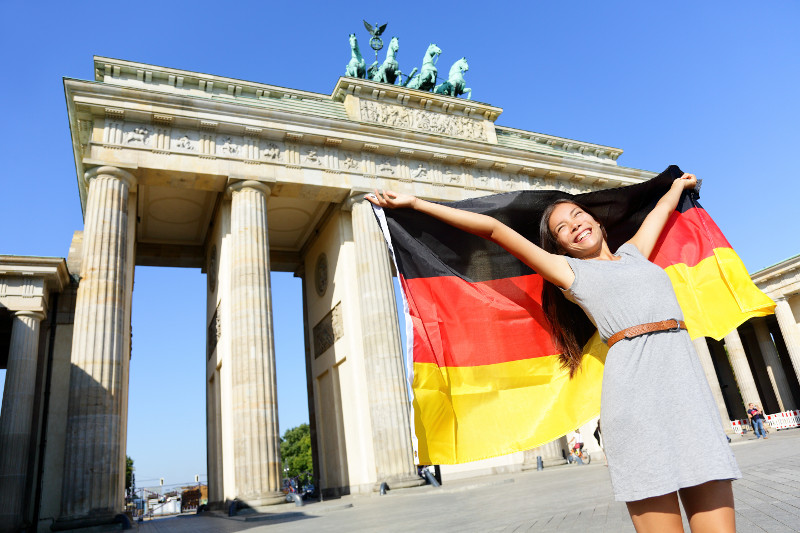 happy young woman with flag of Germany in front of Brandenburger Tor in Berlin